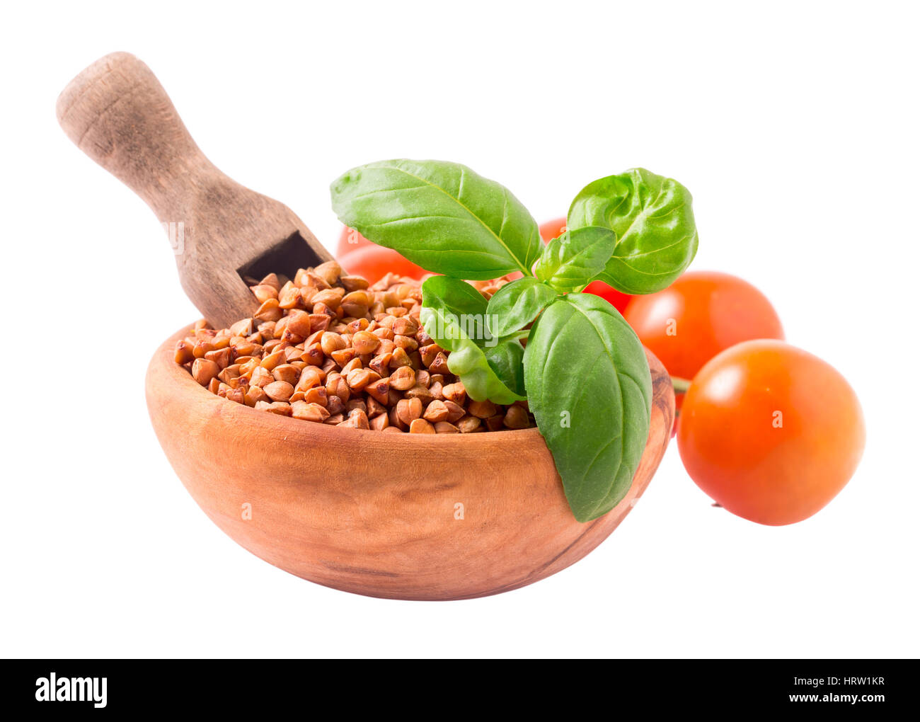 Wooden bowl of uncooked buckwheat groats with scoop and basil leaves. Isolated on white background - Stock Image