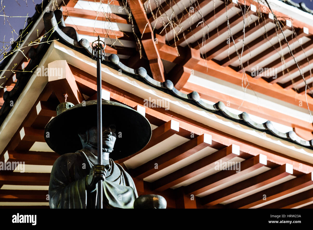A stoic monk, waiting under the eaves of a Japanese temple. - Stock Image