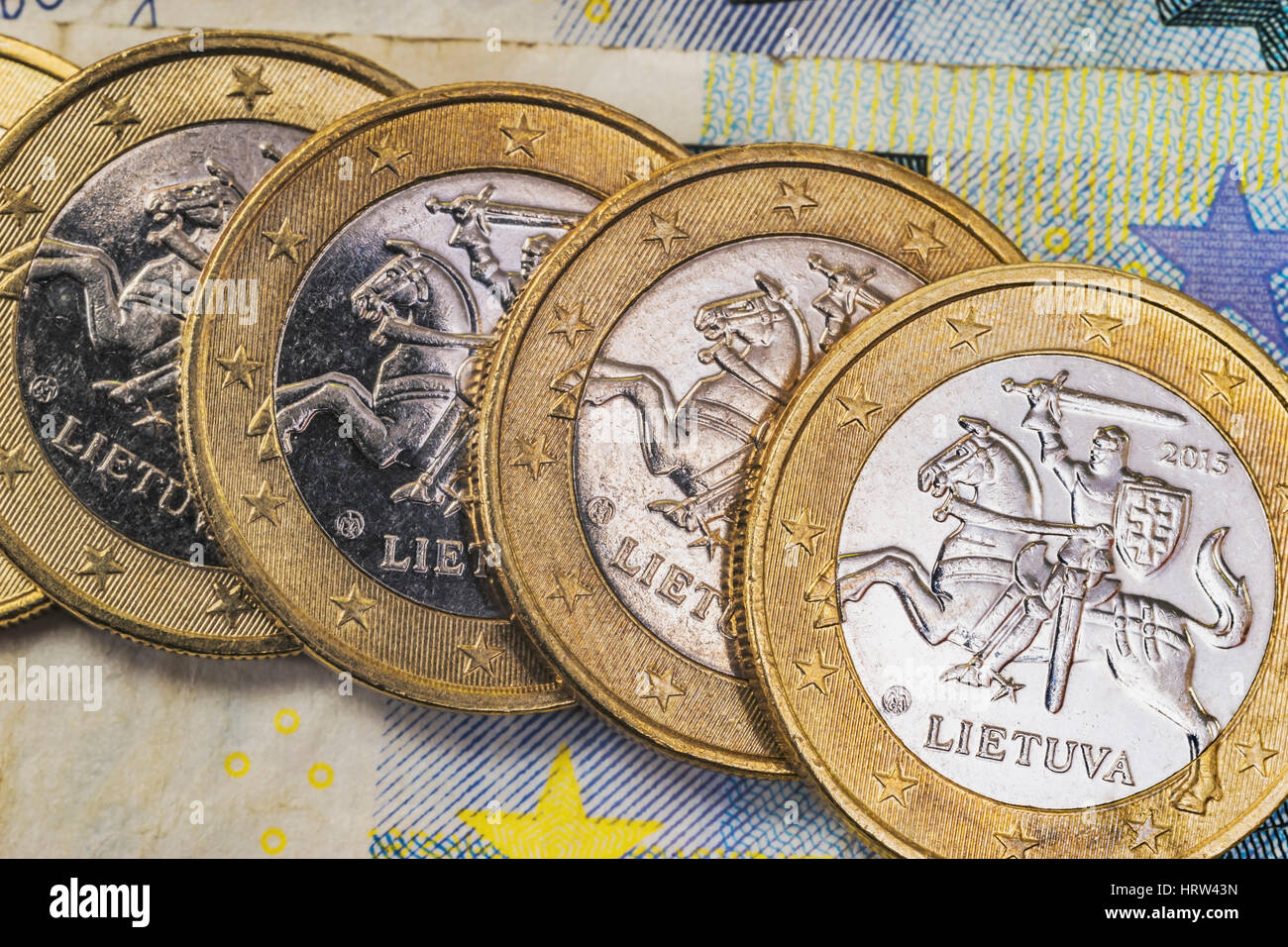 four 1 euro coins from Lithuania on euro banknotes - Stock Image