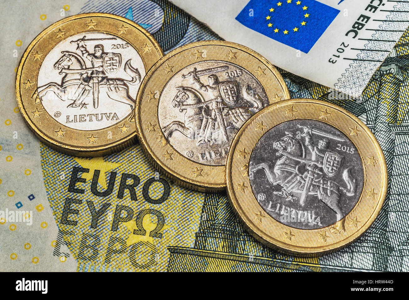 On a 5 euro banknote are three 1 euro coins of the Baltic State Lithuania - Stock Image