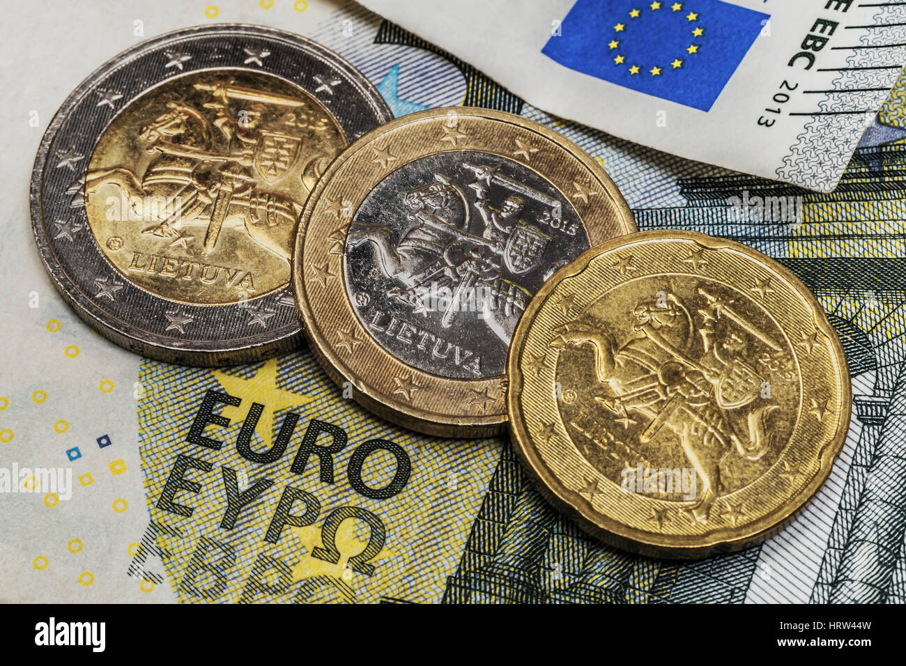 On a 5 euro banknote are three euro coins of the Baltic State Lithuania - Stock Image