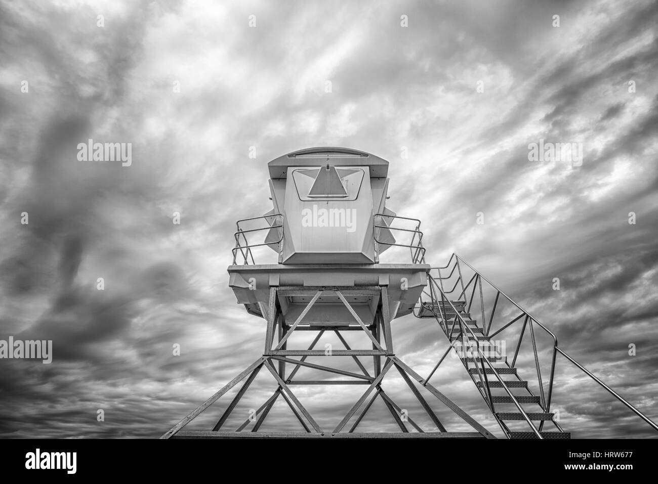 Low angle view of a lifeguard tower against a cloudy sky. Black and white image. - Stock Image
