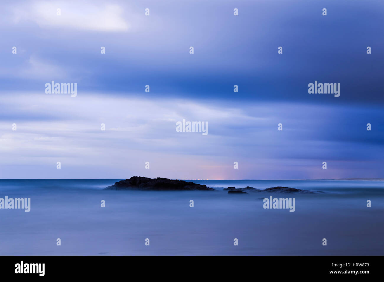 BLue hour over Pacific ocean horizon at Stockton beach in Australia. Minimalistic seascape with blurred waves and - Stock Image