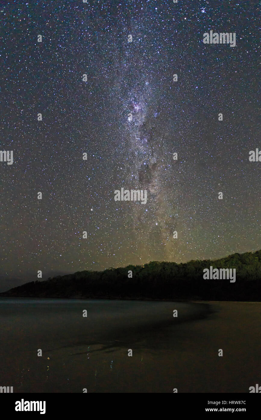 Milky way galaxy with southern cross constellation seen from sandy beach in Australia. Image contains noise and - Stock Image