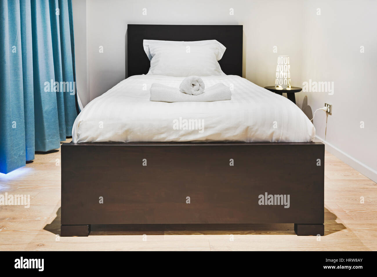 Single Bed With Linen, Bed Side Table And Lamp In A Modern Clean Bedroom