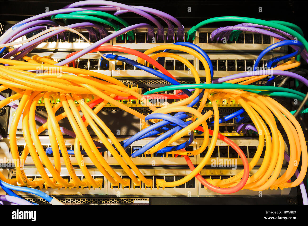 Patch panels, sockets, patch cables connected to the network equipment inside the rack of Data Centre. - Stock Image
