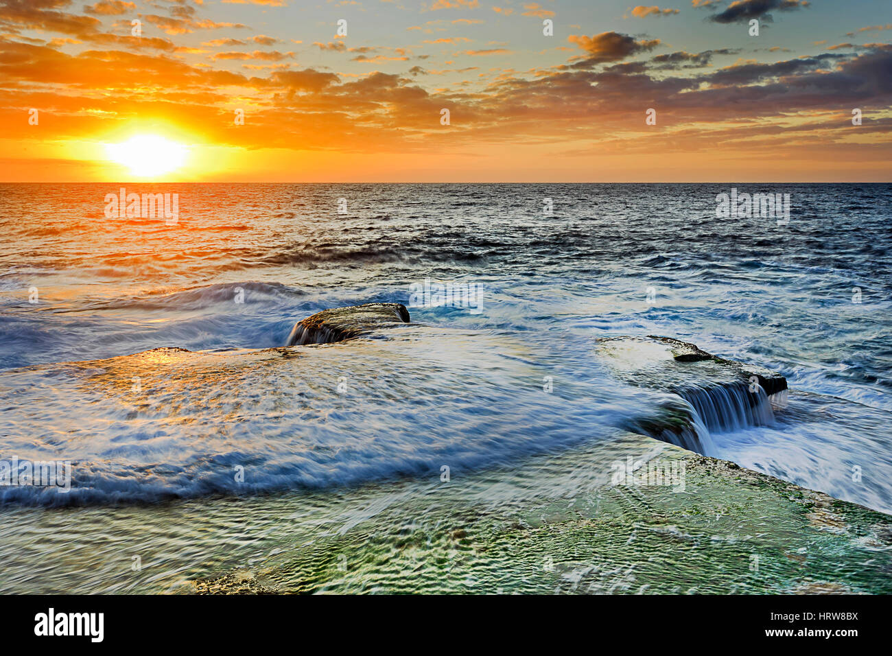 Colourful bright sunrise over horizon from Maroubra beach in Sydney. Incoming wave flows over flat coastal rocks - Stock Image