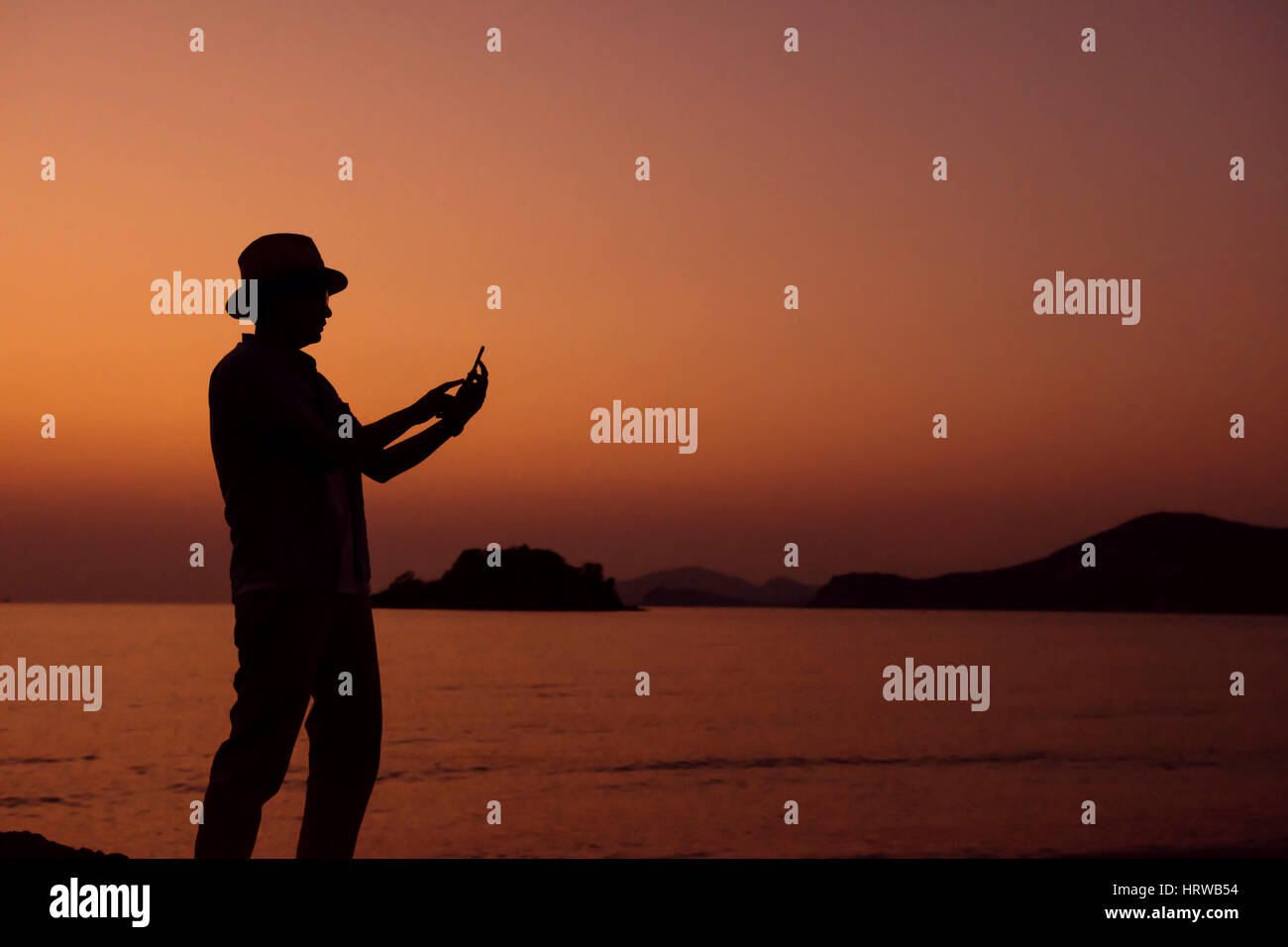 Silhouette of human using smart phone in Sunset at Beach, always connected concept - Stock Image