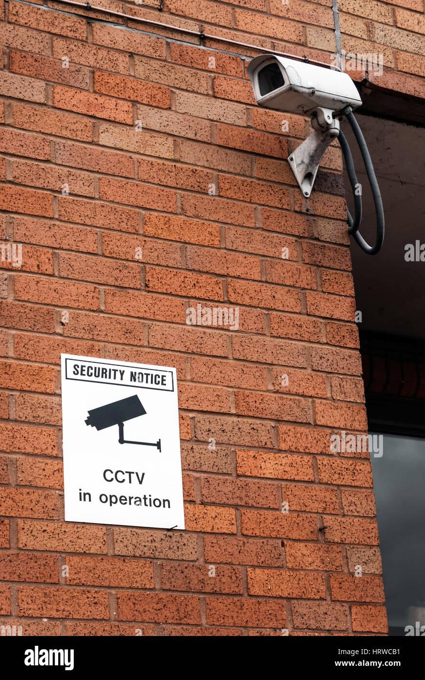 CCTV camera and warning notice on urban red brick wall - Stock Image