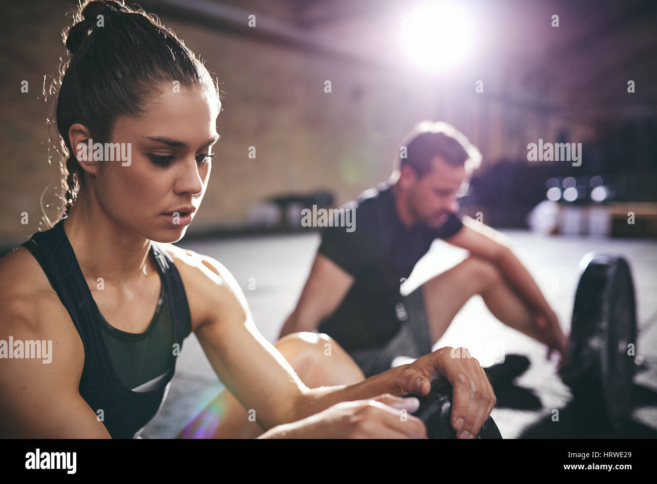 Sportive people sitting and recreating in gym. Horizontal indoors shot - Stock Image