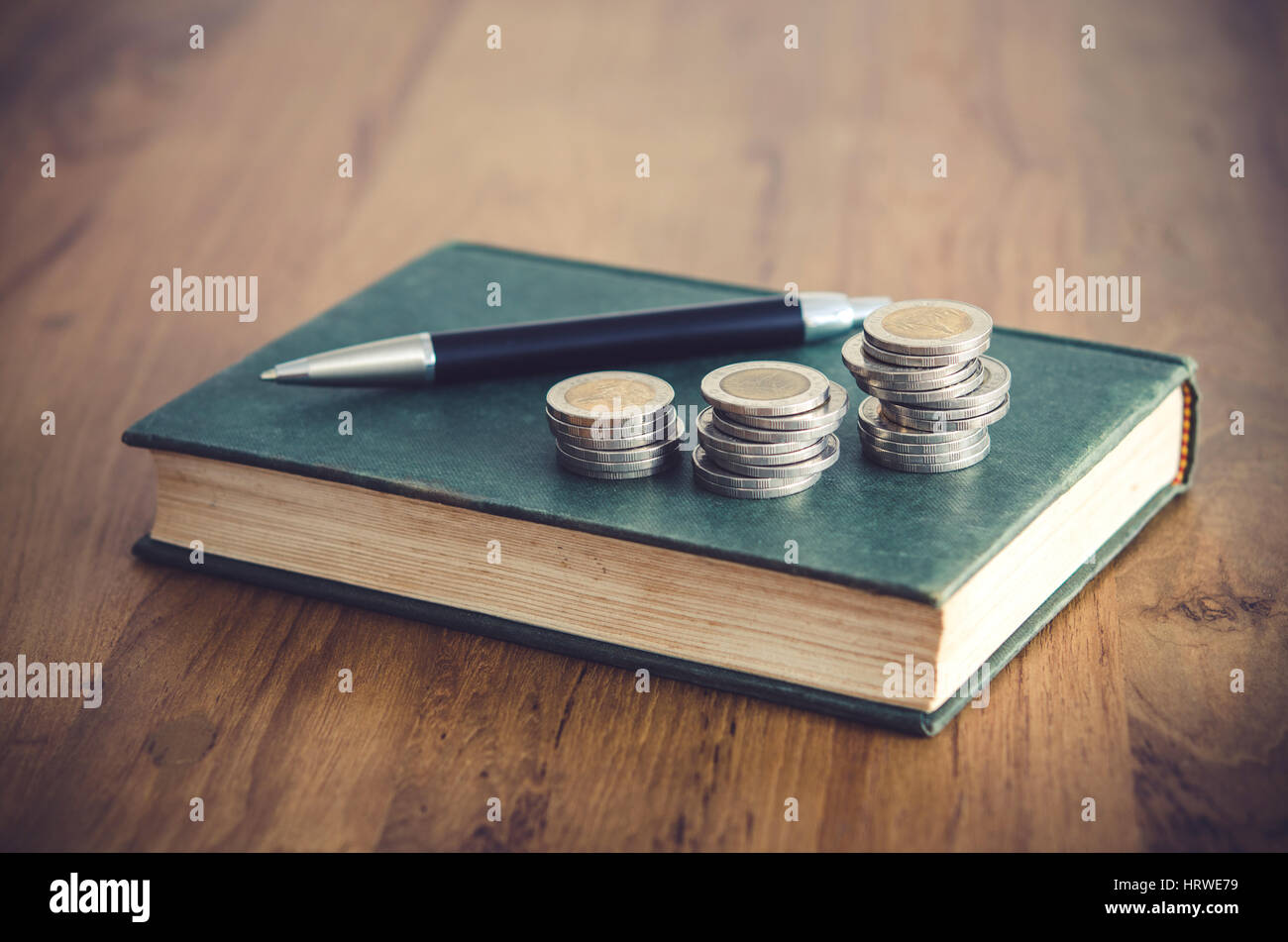 Business concept. Closeup stack of coins, pen and old book on wooden table. - Stock Image