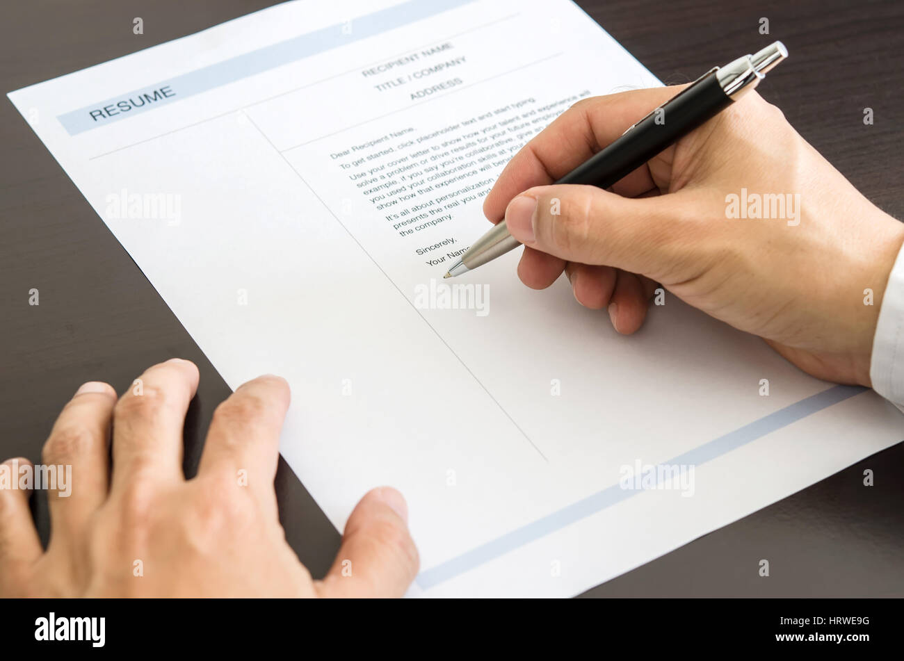 close up businessman or job seeker signing on resume form stock