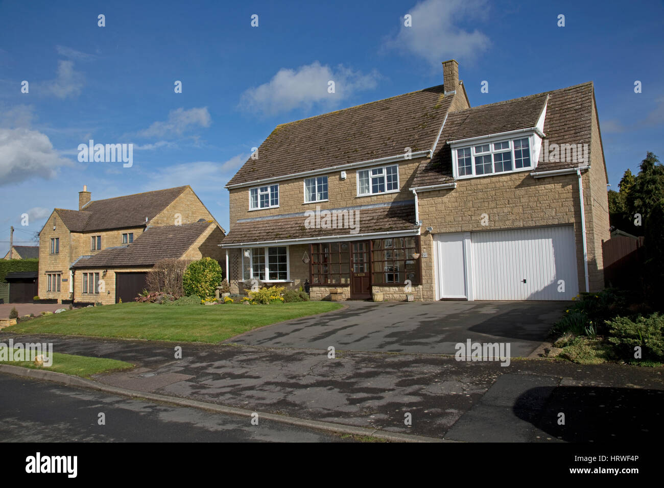Large detached Cotswold stone substantial family houses double garage landscaped gardens Mickleton UK - Stock Image