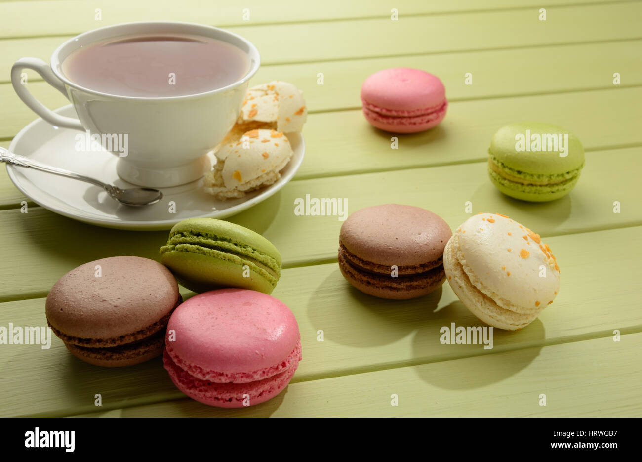 Tasty varicolored macarons and cup of tea on a green wooden table. - Stock Image