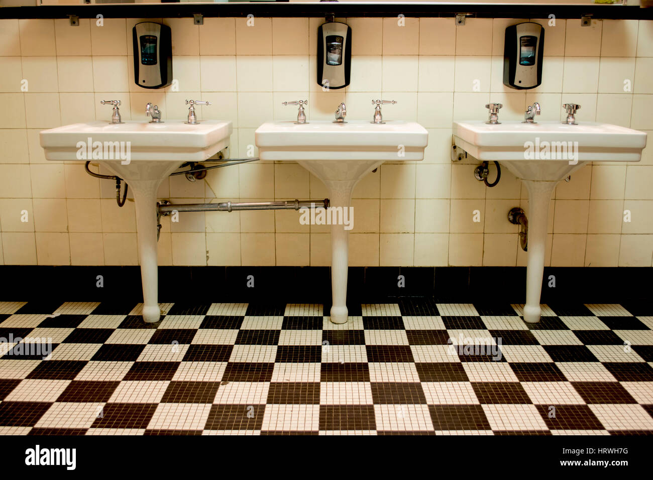Three white porcelain sinks in an old Art Deco public bathroom with ...
