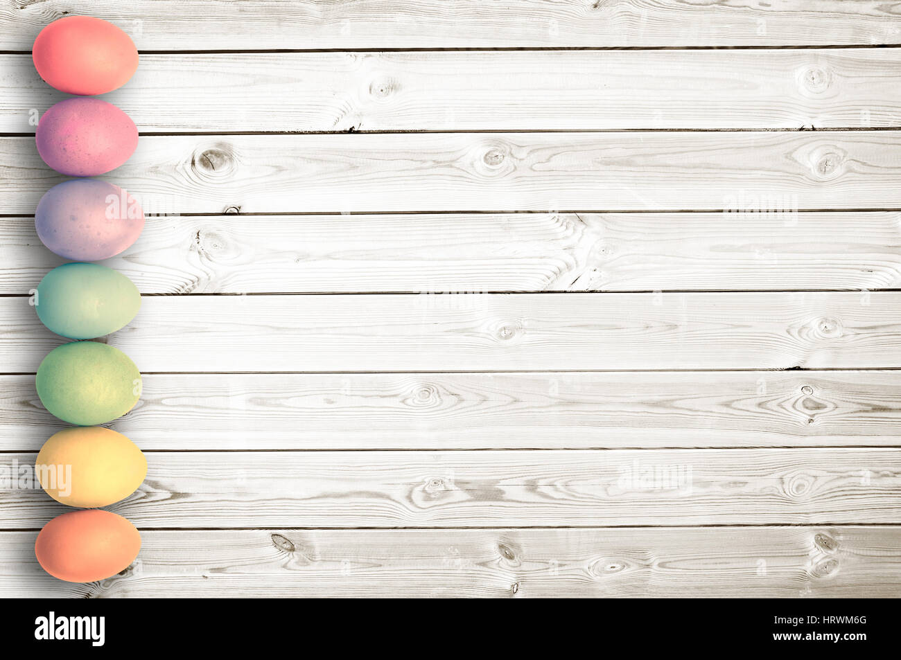 Pastel colored eggs on white wooden planks, easter background - Stock Image