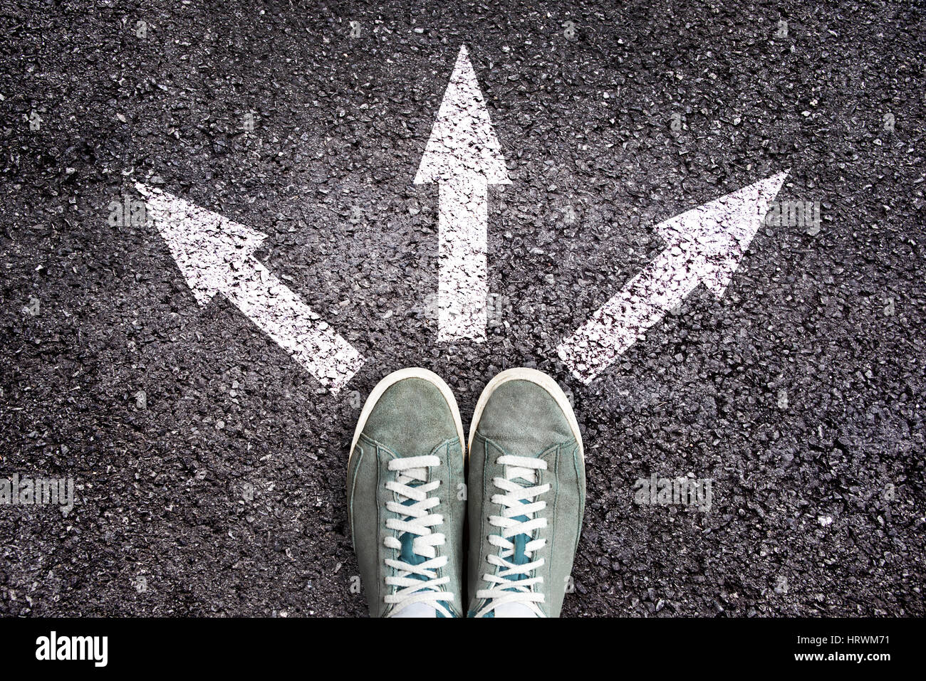 Shoes and arrows pointing in different directions on asphalt floor - Stock Image