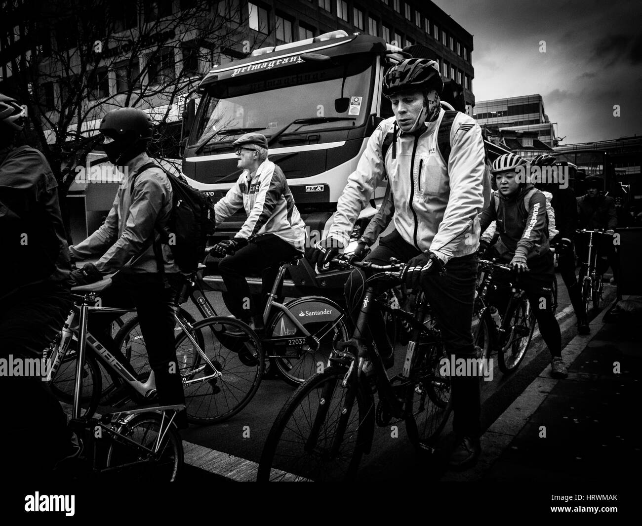 A cyclist, who looks like he's got the weight of the world on his shoulders, waits at traffic lights at London - Stock Image
