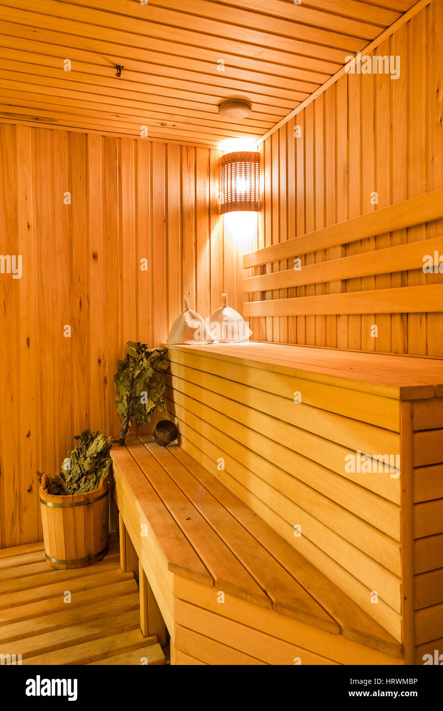 Interior of a sauna . Advantage for health. Oak brooms for a steam room in traditional russian wooden bath. - Stock Image