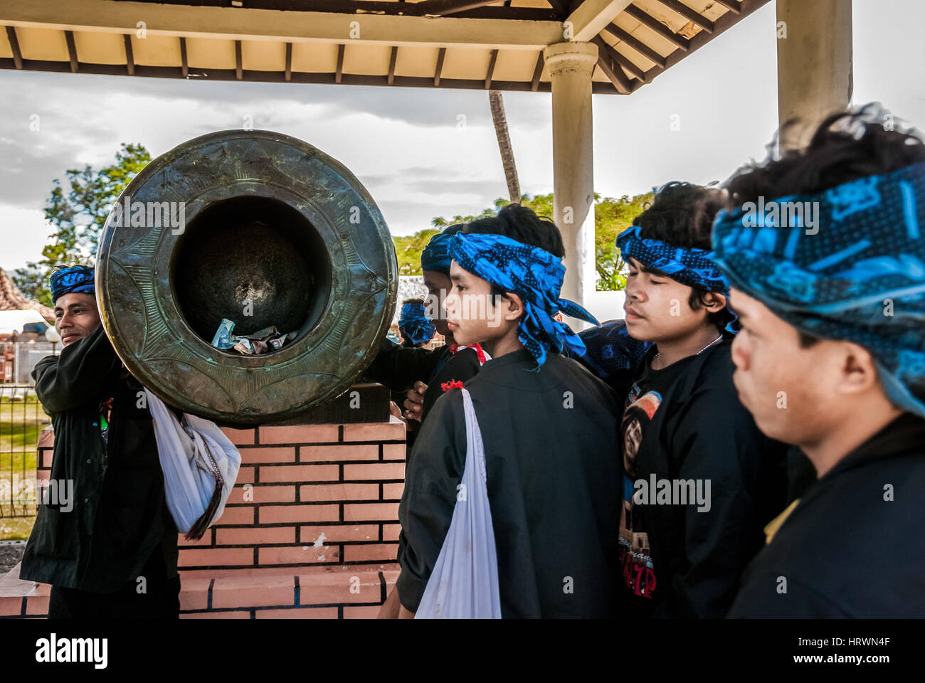 Sundanese indigenous people of Baduy pay attention to an ancient cannon in Banten, Indonesia. © Reynold Sumayku - Stock Image