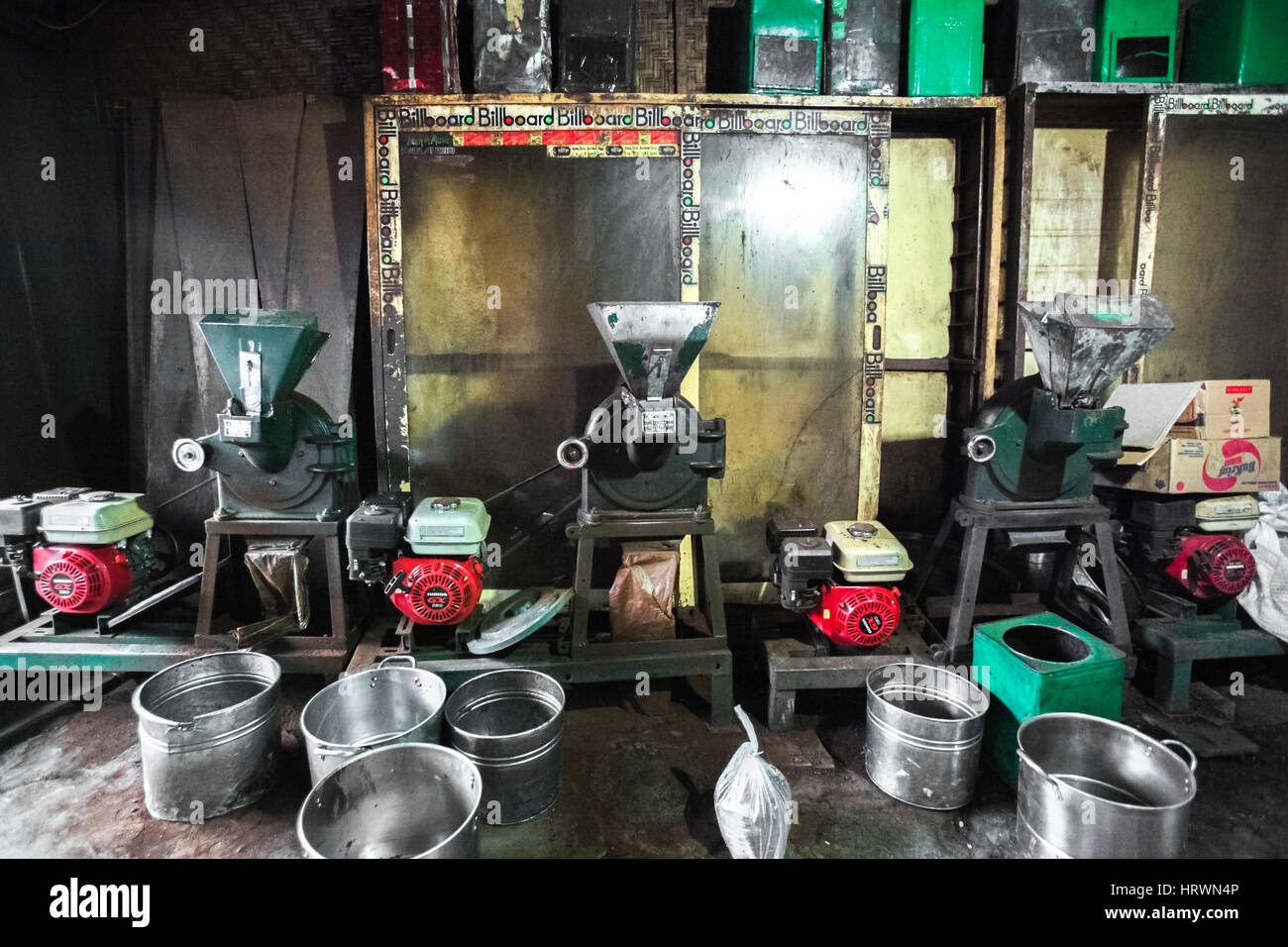 Old-fashioned coffee grinders and pans inside an Asian coffee roasting warehouse. - Stock Image