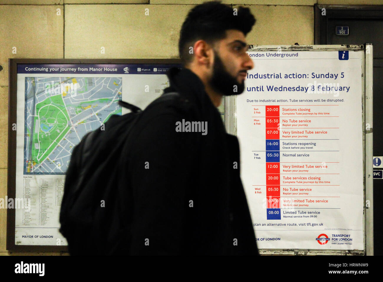 Commuters pass by a London underground tube strike poster displayed at Manor House. Industrial action is due to - Stock Image