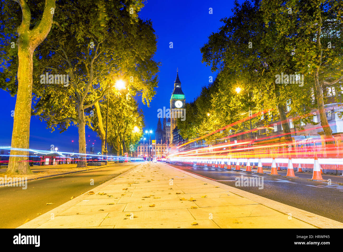 Cityscape of a Street in Westminster with Big Ben in the distance at night - Stock Image