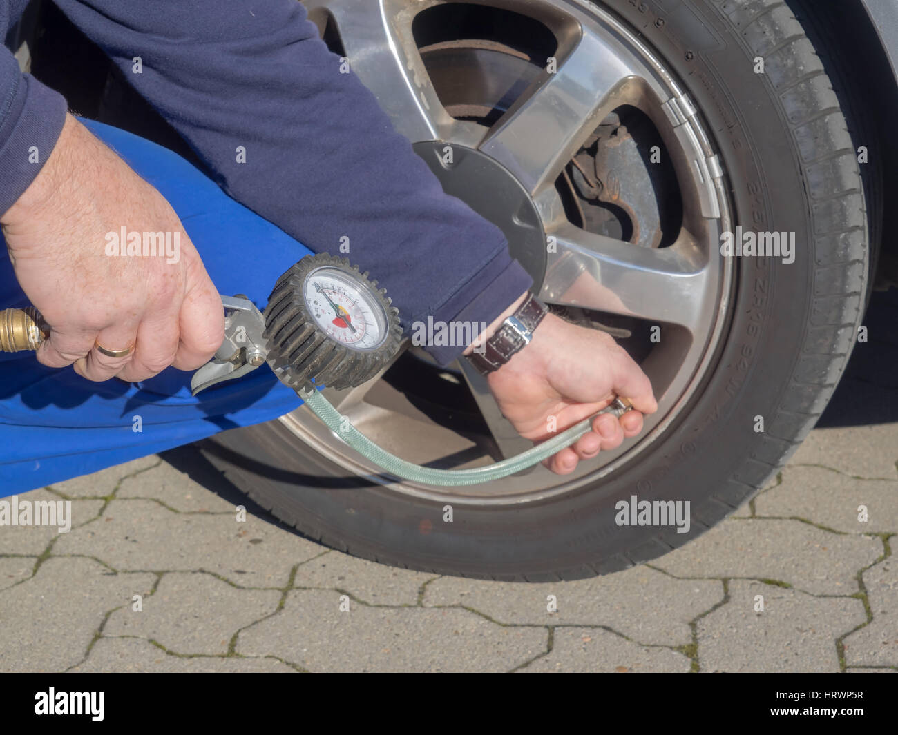 A man is measuring the air pressure of the tire of a car - Stock Image