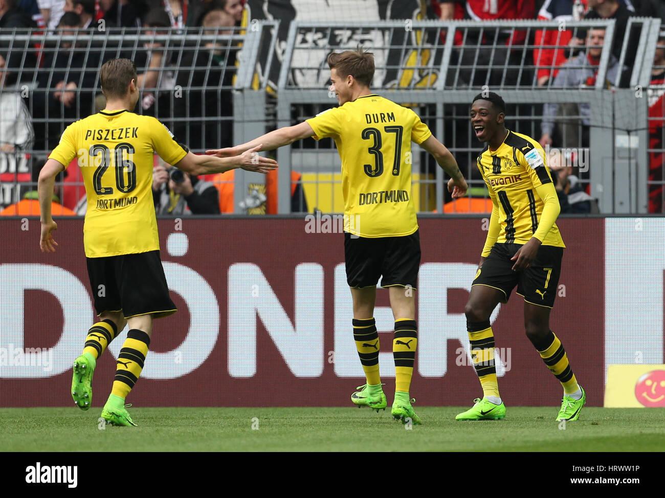 Dortmund's goal scorer Ousmane Dembele cheers with team mates Lukasz Piszczek (l) snd Erik Durm after scoring - Stock Image
