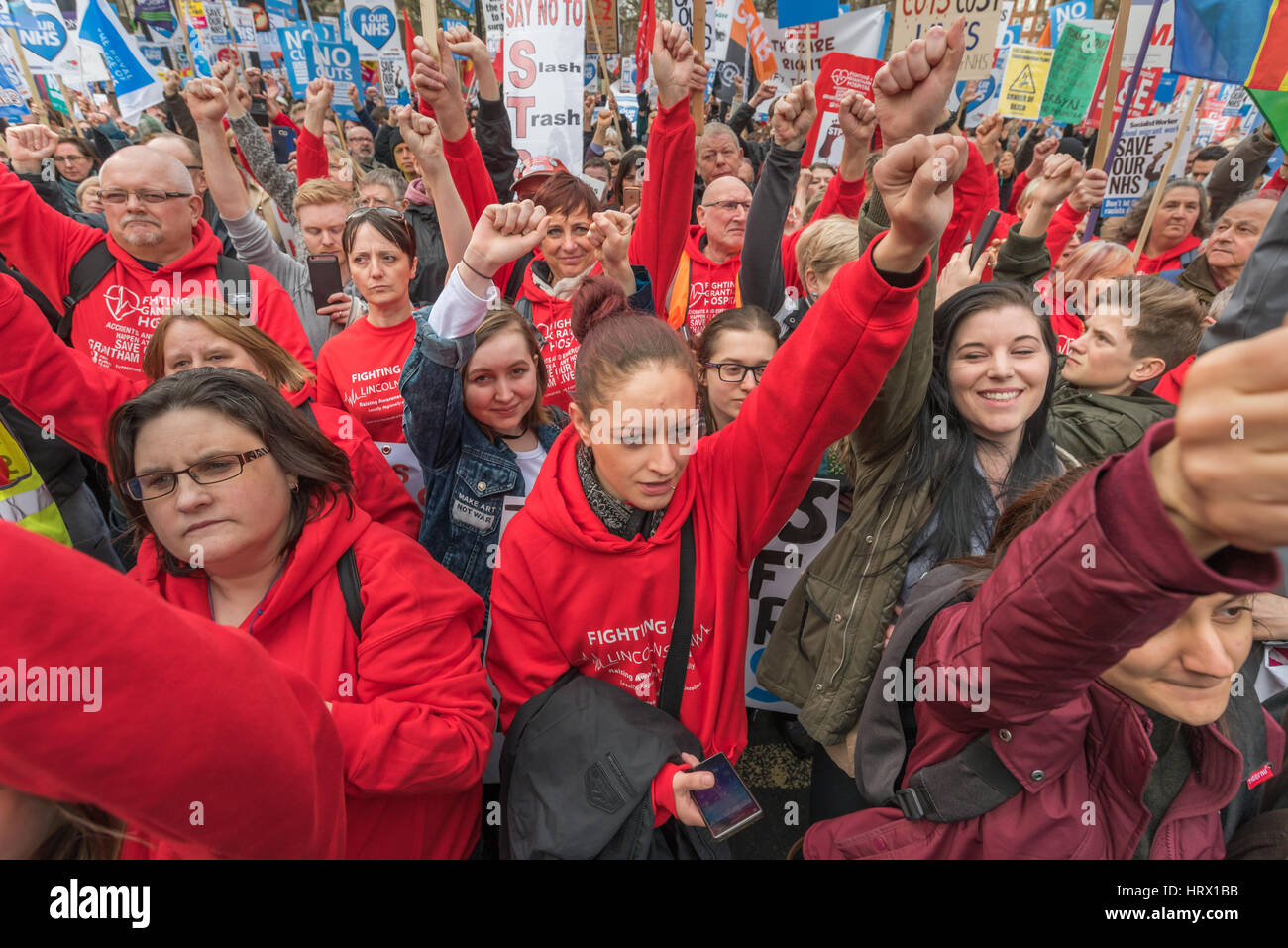 London, UK. 4th March 2017. The crowd raises fists to respond to a speaker at the rally before thousands march though - Stock Image