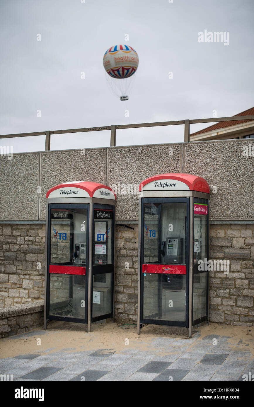 Two telephone boxes against a wall in the street with the Bournemouth Balloon, a tourist attraction, floating in - Stock Image