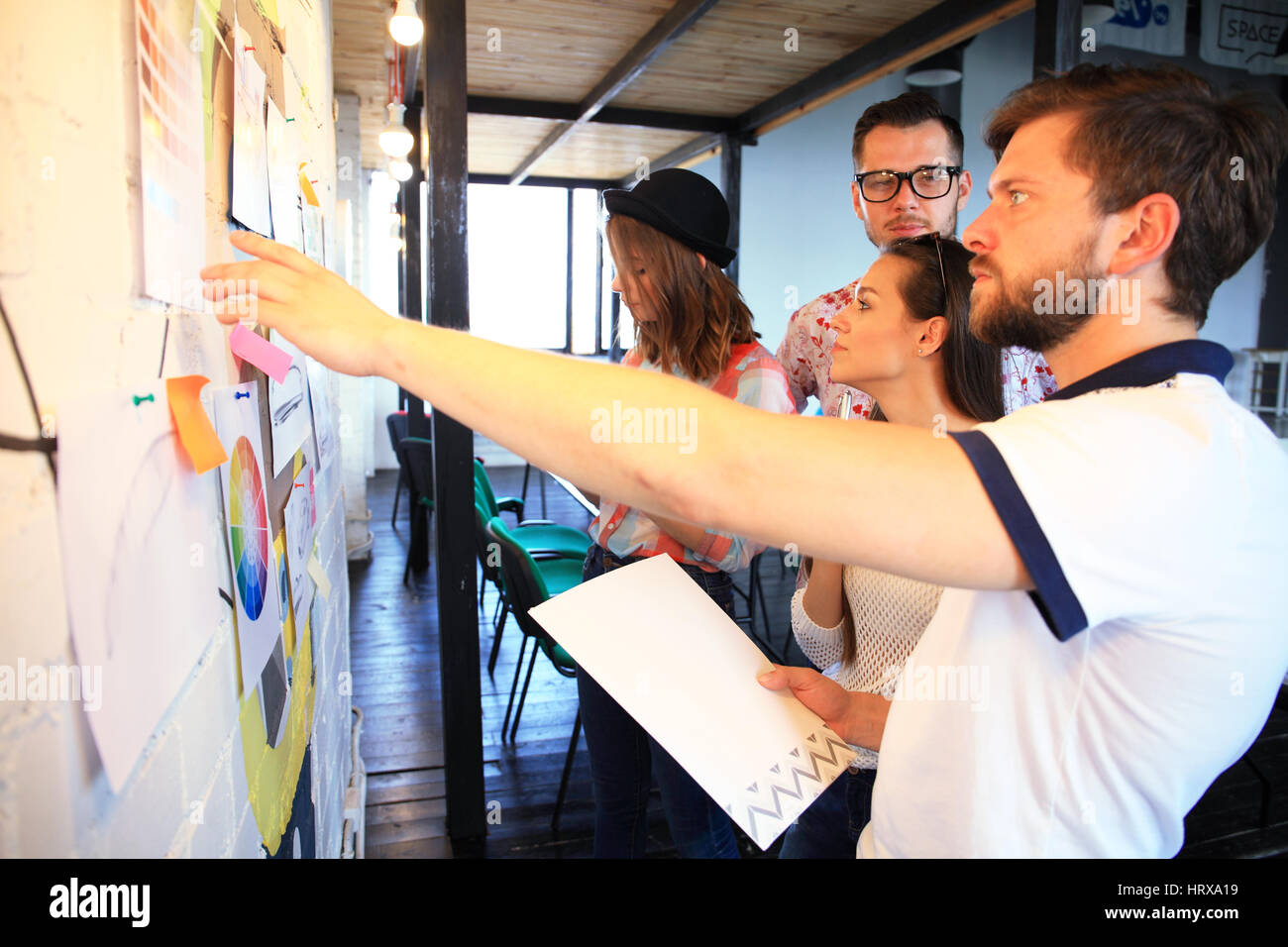 Businessman with young partners looking at whiteboard in creative office - Stock Image