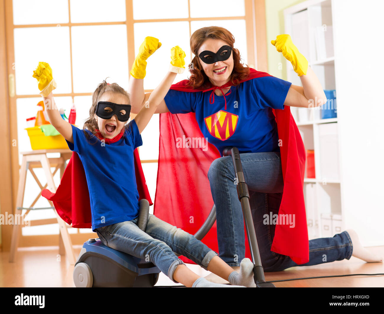 Strong superhero housewife and kid daughter ready to room cleaning. Housework and household concept. - Stock Image