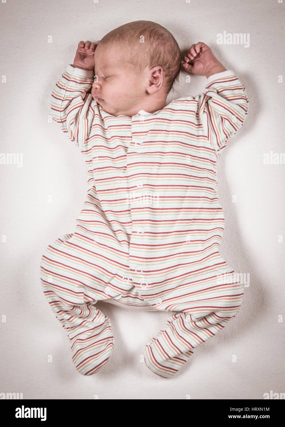 Baby asleep stretched out in a babygrow - Stock Image