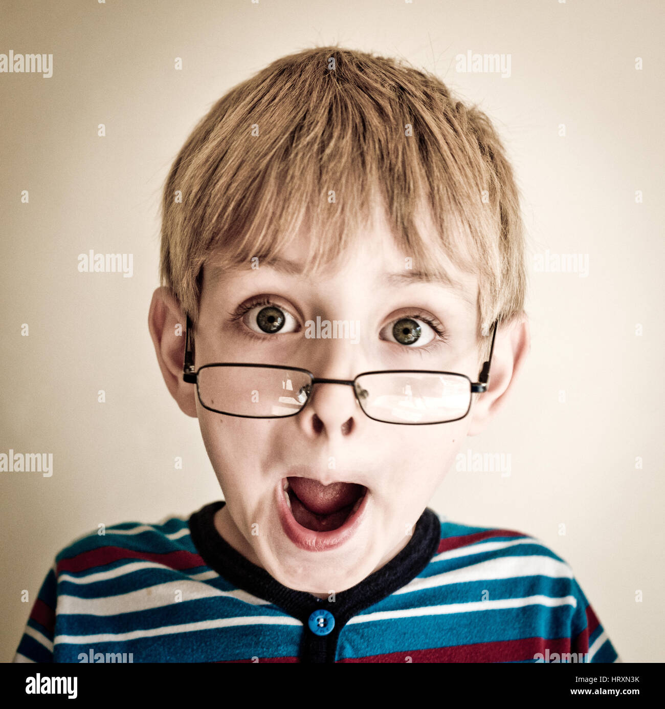 A young blonde haired boy with glasses with an expression of surprise on his face. - Stock Image