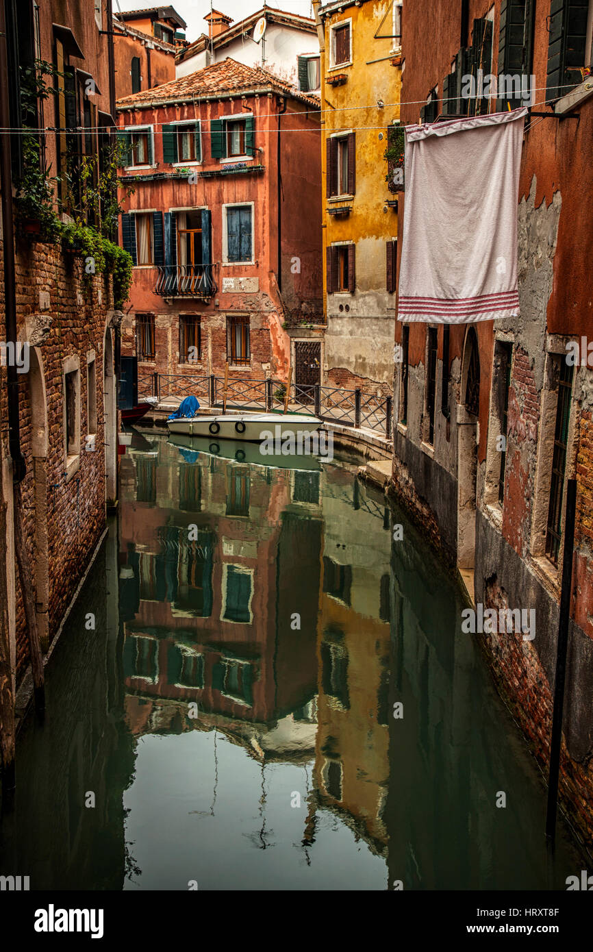 Quiet canal with hanging laundry in a residential area of Venice, Italy - Stock Image