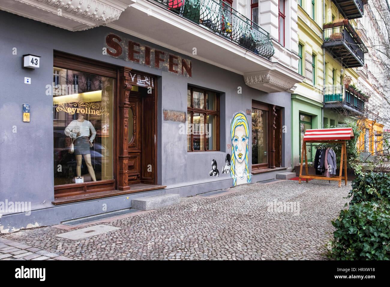 Berlin, Prenzlauer Berg. Street scene, Cyroline Upmarket clothing shop,old preserved shop sign and El Bocho street art Stock Photo