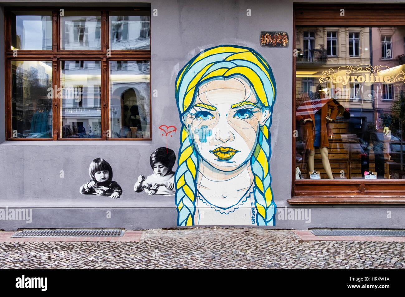 Berlin, Prenzlauer Berg. Street scene, Cyroline Upmarket clothing shop exterior and El Bocho street art - Stock Image