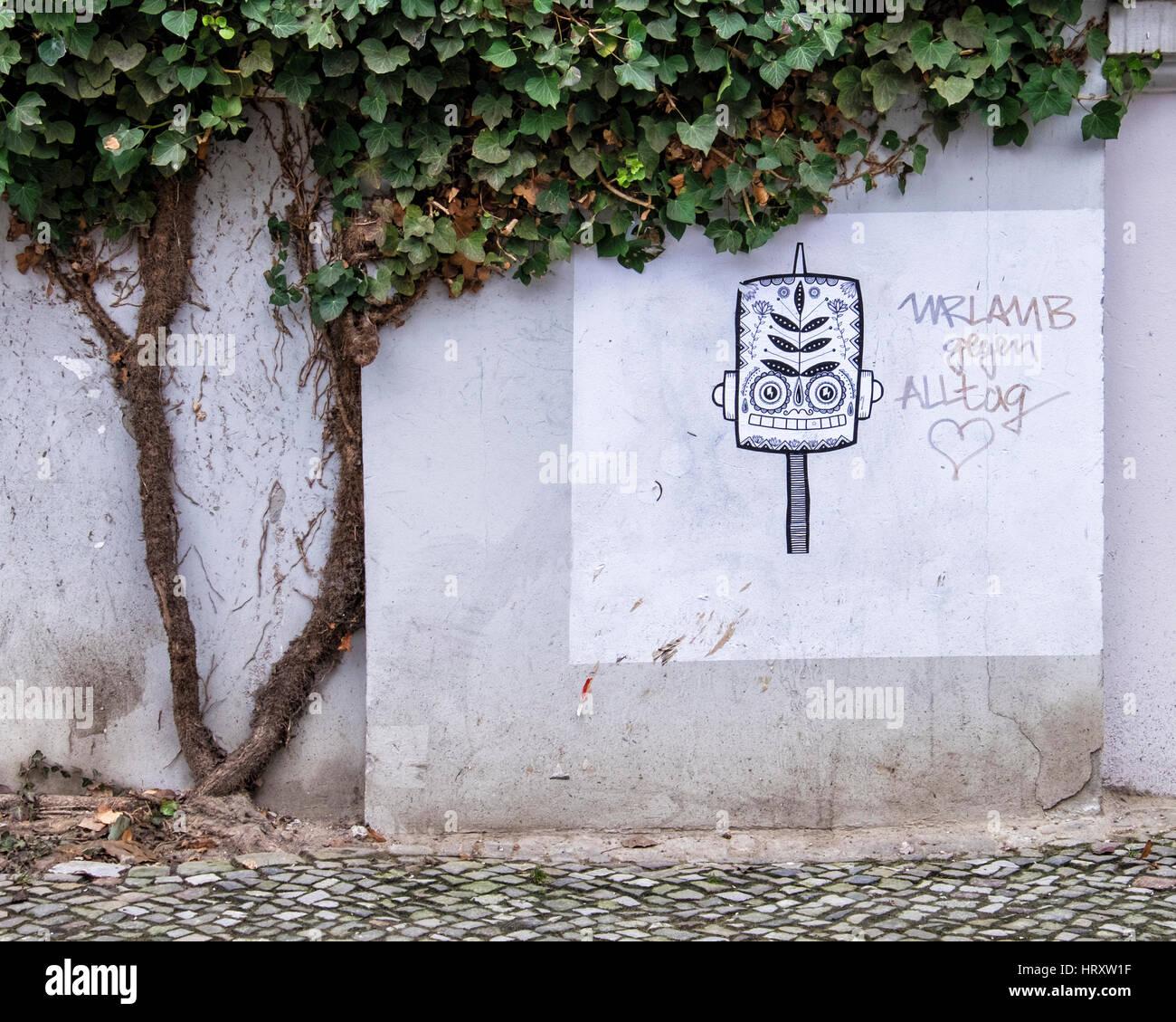 Berlin, Prenzlauer Berg..Street art. pattern face and 'Urlaub gegen Alltag' meaning 'holiday against - Stock Image