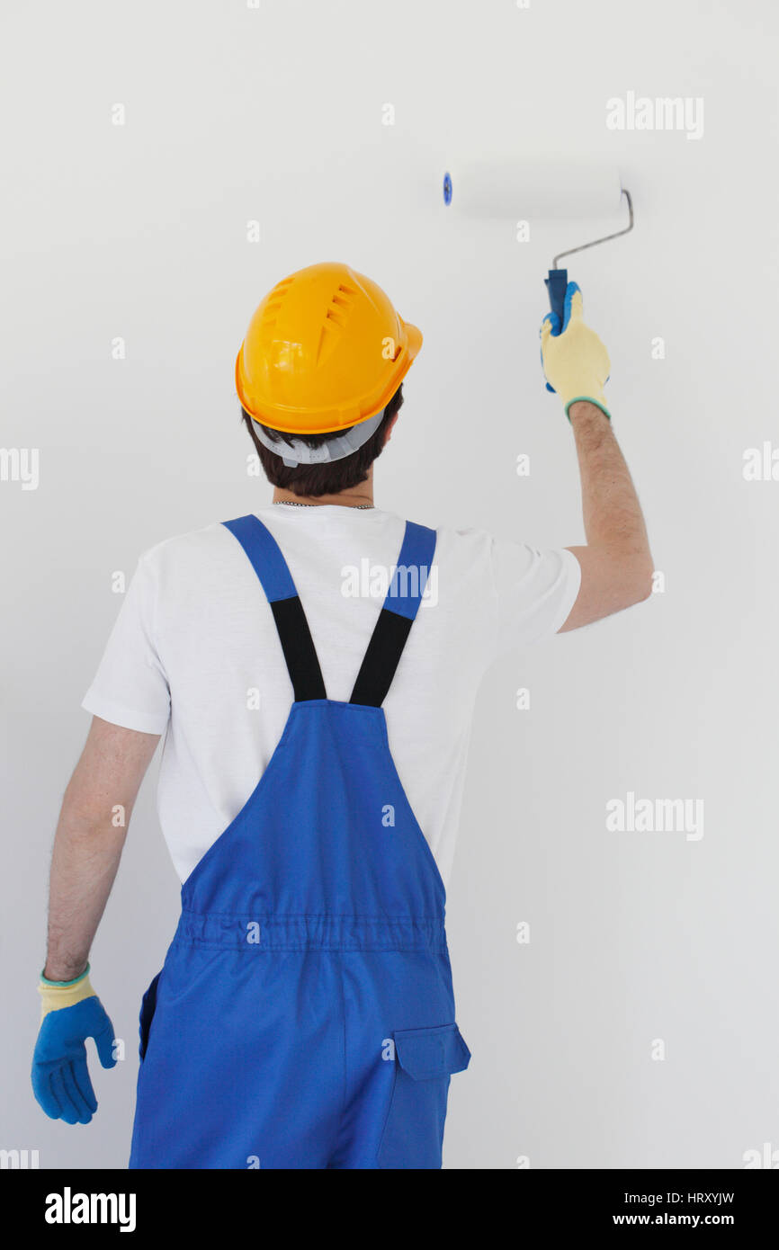 Worker in overalls uniform and hardhat painting the wall with paint roller - Stock Image