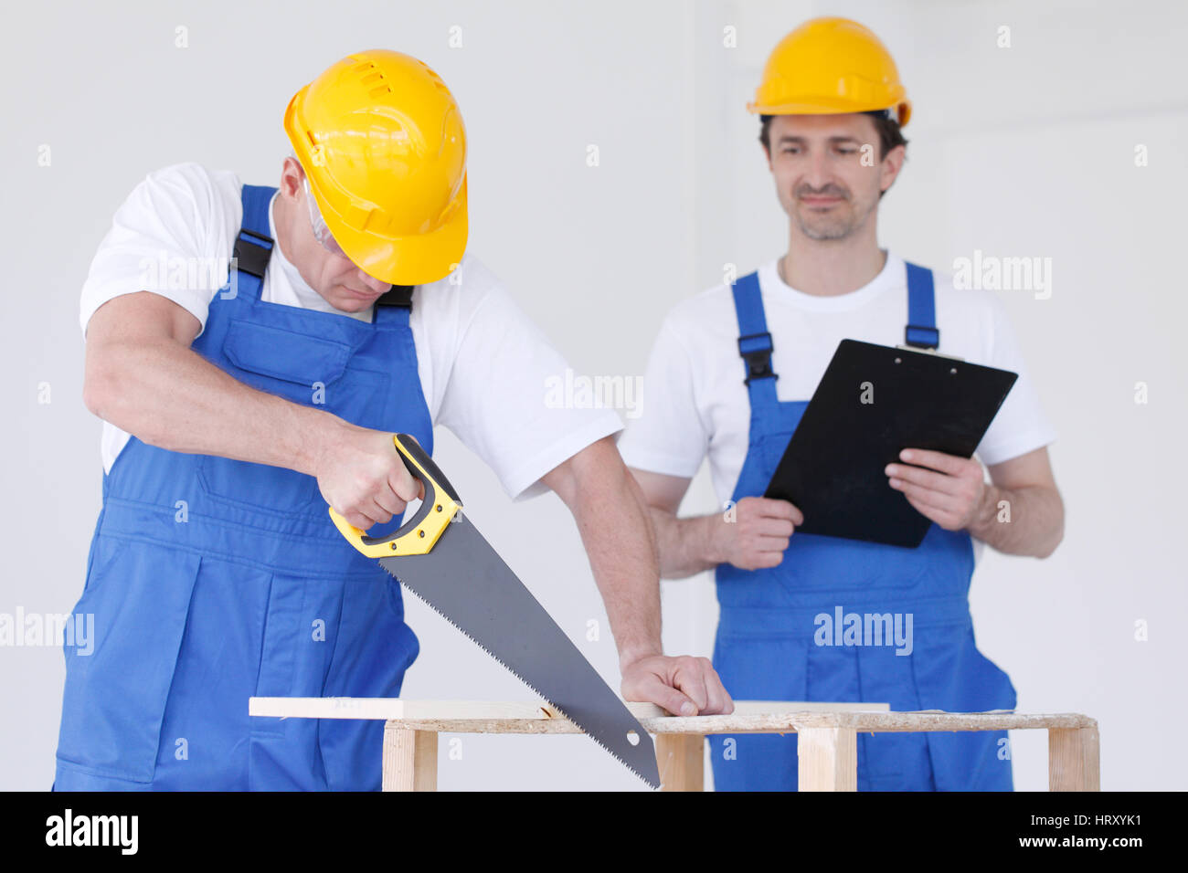 Two workmen in protective workwear with saw and folder - Stock Image