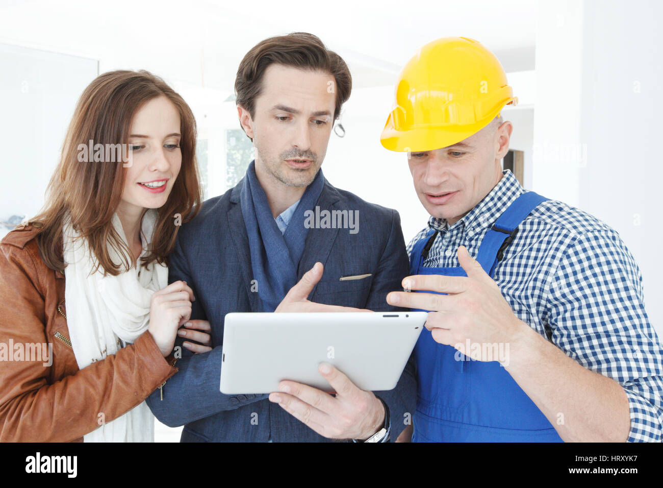 Worker and couple using tablet pc at construction site - Stock Image