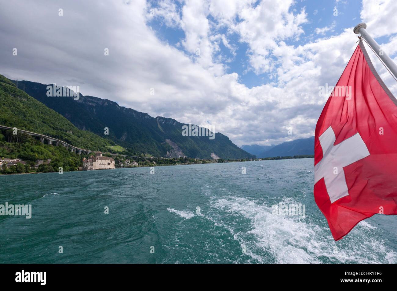 Swish flag and the Chillon Castle on Lake Geneva (Lac Léman) from the Steam boat  , Veytaux, 	Switzerland - Stock Image