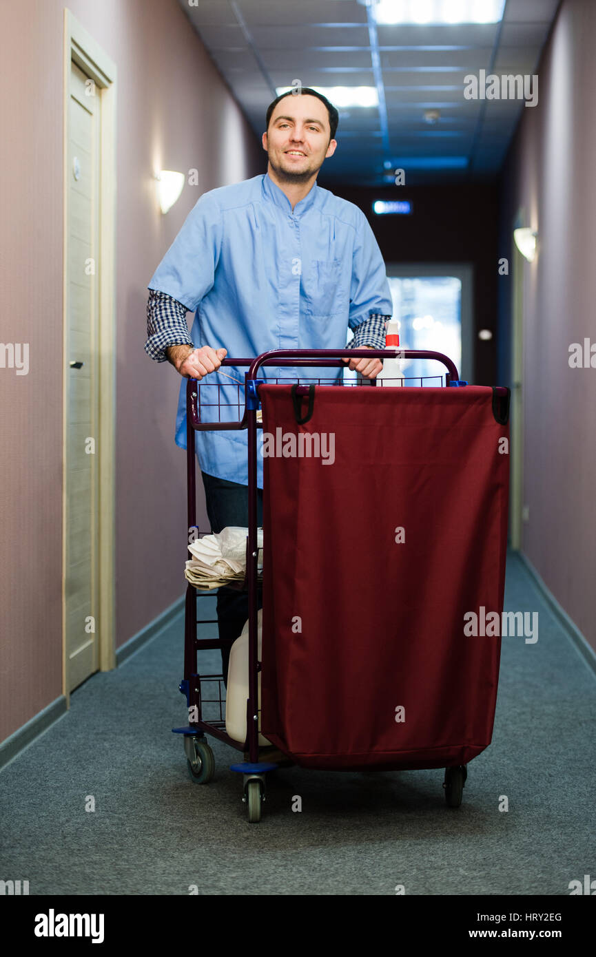 Young man pushing a housekeeping cart laden with clean towels, laundry and cleaning equipment in a hotel as he services - Stock Image