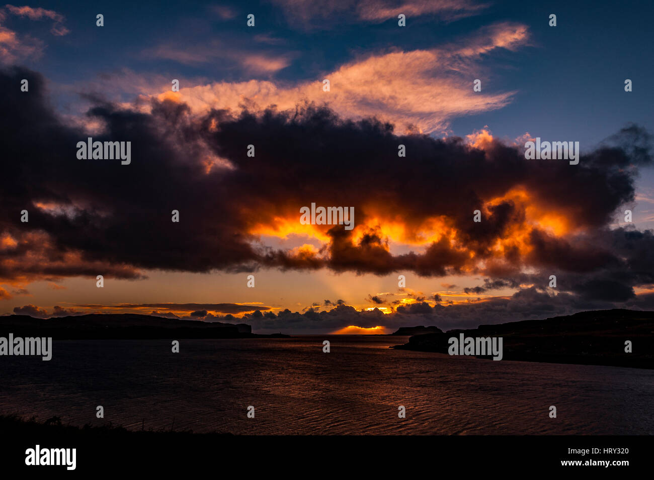 Sunset with crepuscular light across Loch Beag, Isle of Skye, looking out to Ullinish Point, Bracdale Point, Ardtreck Point and Isle Oronsay Stock Photo