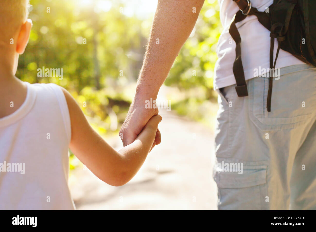 child holding hand of adult parent outside in summer park - Stock Image