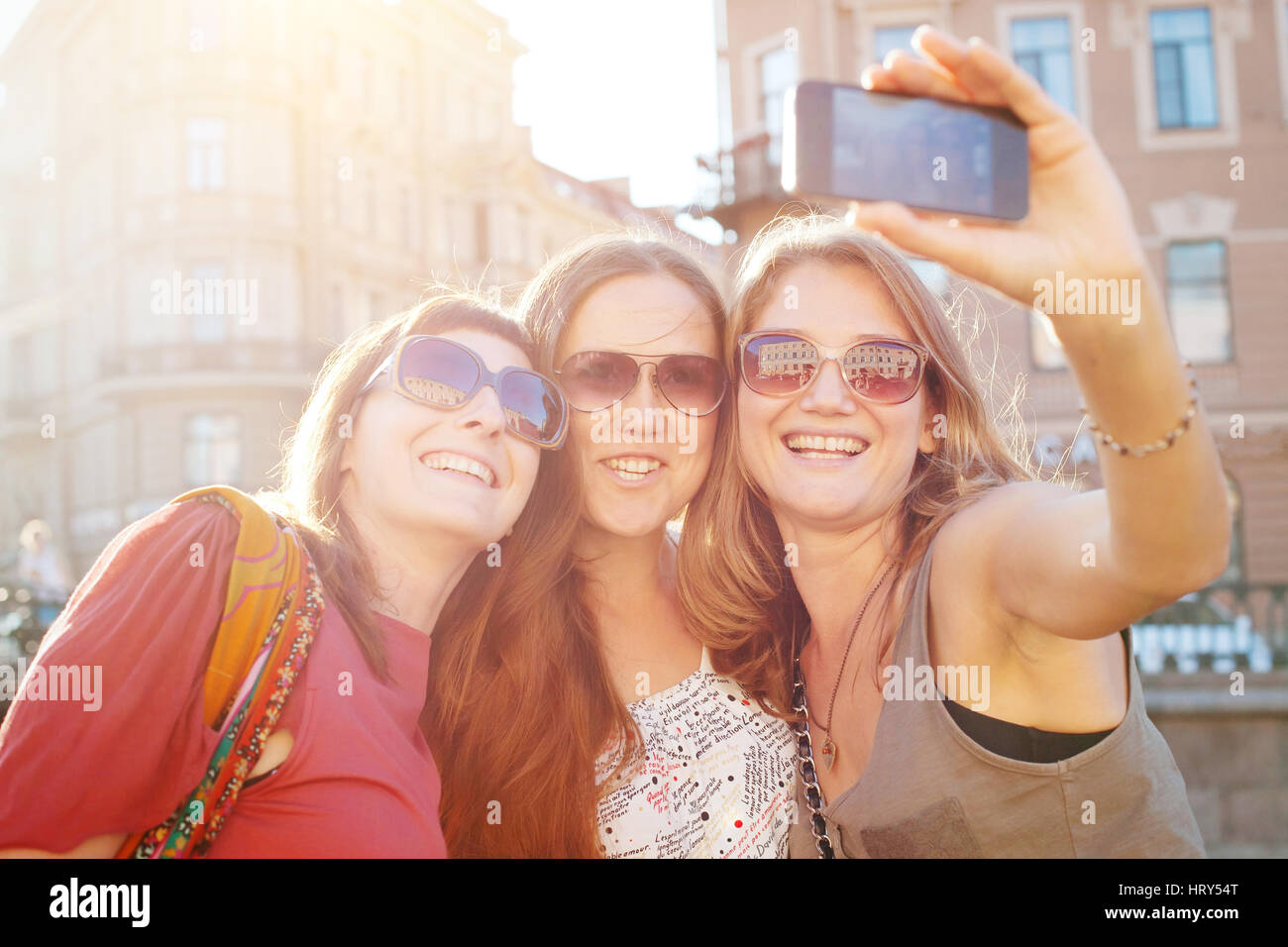 tourists in european city, travel in Europe, group of happy friends taking photo selfy - Stock Image