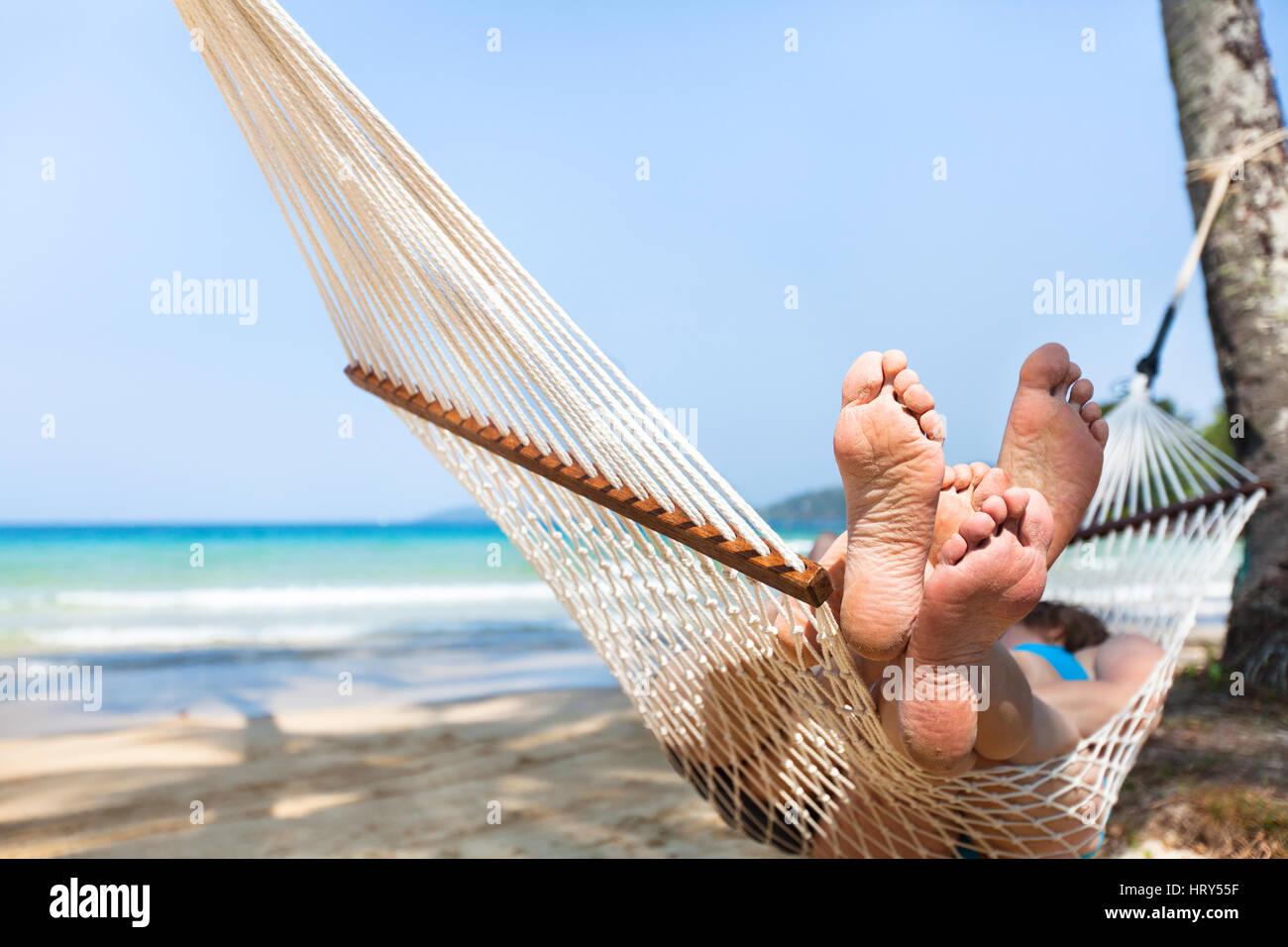 happy couple family in hammock on tropical paradise beach, island holidays, closeup of feet - Stock Image