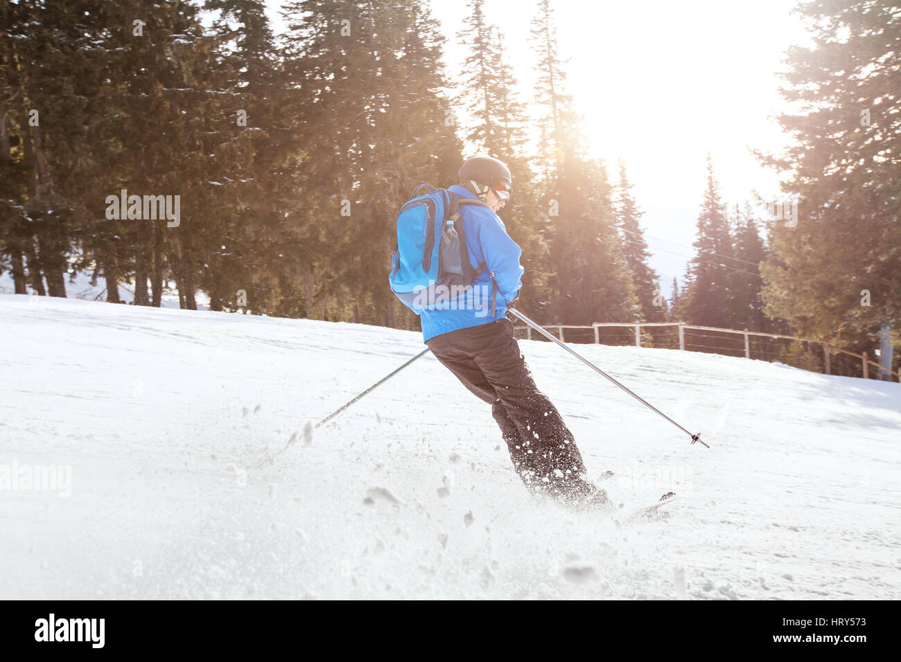 downhill skiing at sunset, beautiful skier in motion - Stock Image