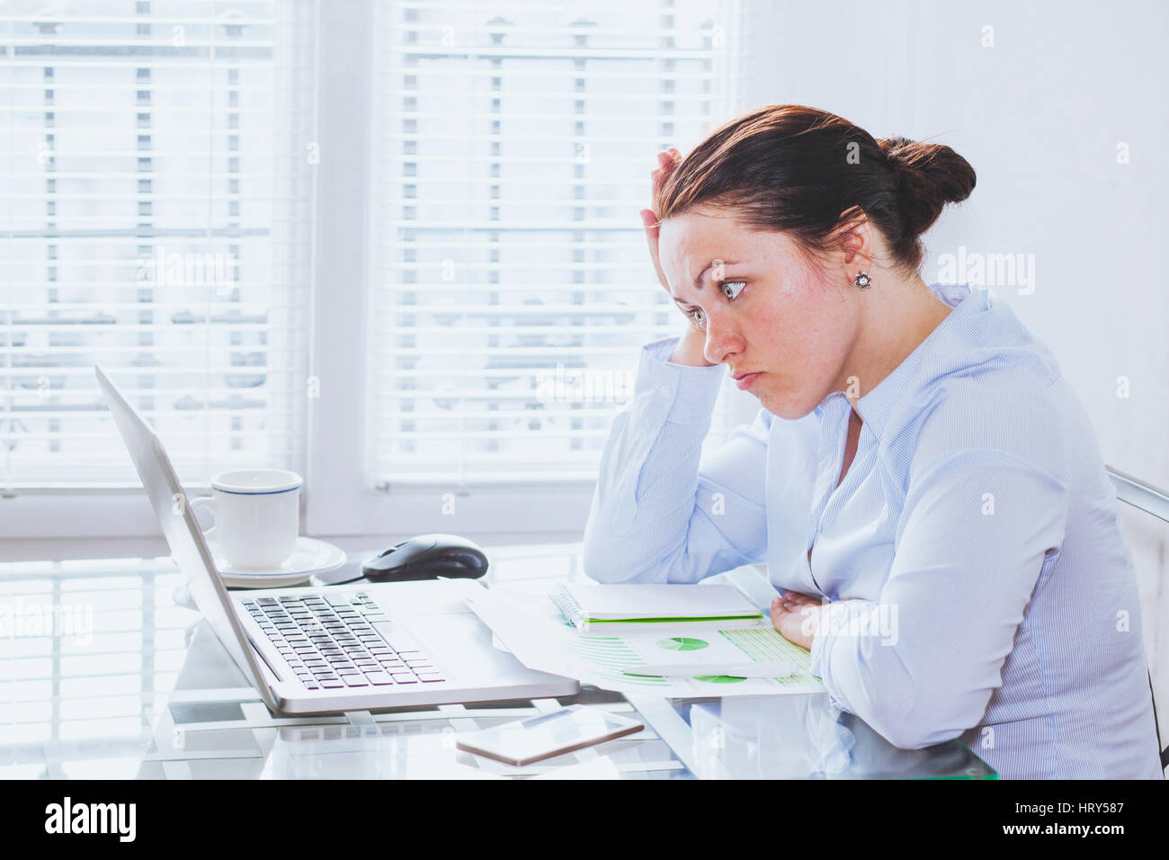 angry furious woman in modern business office looking at screen of laptop computer, anger, annoyed businesswoman - Stock Image